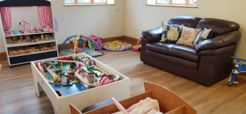 Soft play area in a games room with wooden floor a sofa on the right hand side of the room and soft play toys at the ebck of the room with windows on either side fo the wall