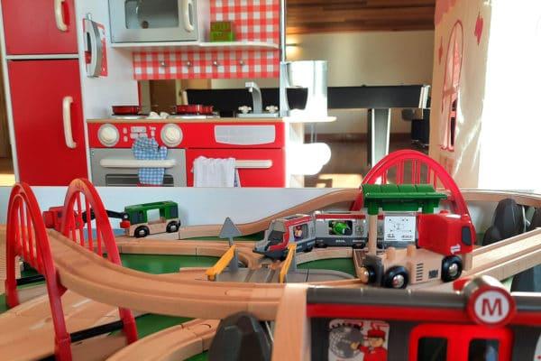 Brio train set, interactive children's play kitchen behind